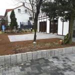 Privatgarten Garbenteich - Mauer aus Granitpalisaden und Terrasse aus Keramikplatten im Hintergrund